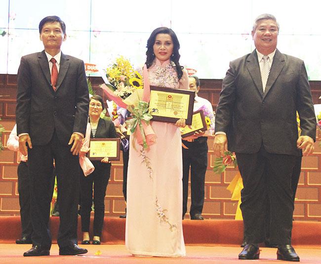 Ông Huỳnh Thành Long (ảnh trái), Phó Chủ tịch HĐND tỉnh và ông Đặng Minh Hưng, Phó Chủ tịch UBND tỉnh trao hoa và biểu trưng cho bà Đặng Thị Kim Oanh, Tổng giám đốc Công ty cổ phần Địa ốc Kim Oanh.